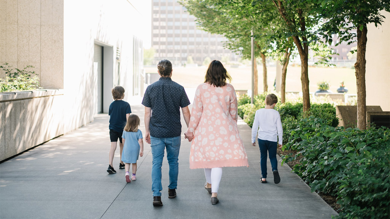 a family of five walks away from the camera on a tree-lined path for a story on disability parenting during the pandemic
