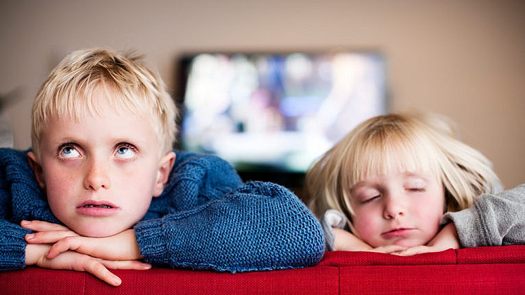 Photo of two siblings looking frustrated sitting on the couch
