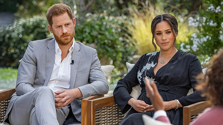 Prince Harry and Meghan Markle seated on an outdoor patio with greenery behind them during their interview with Oprah