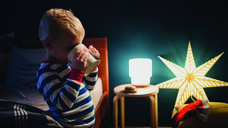 A kid drinking water in his bedroom with lots of night lights on for a story about sleep training six-year-olds