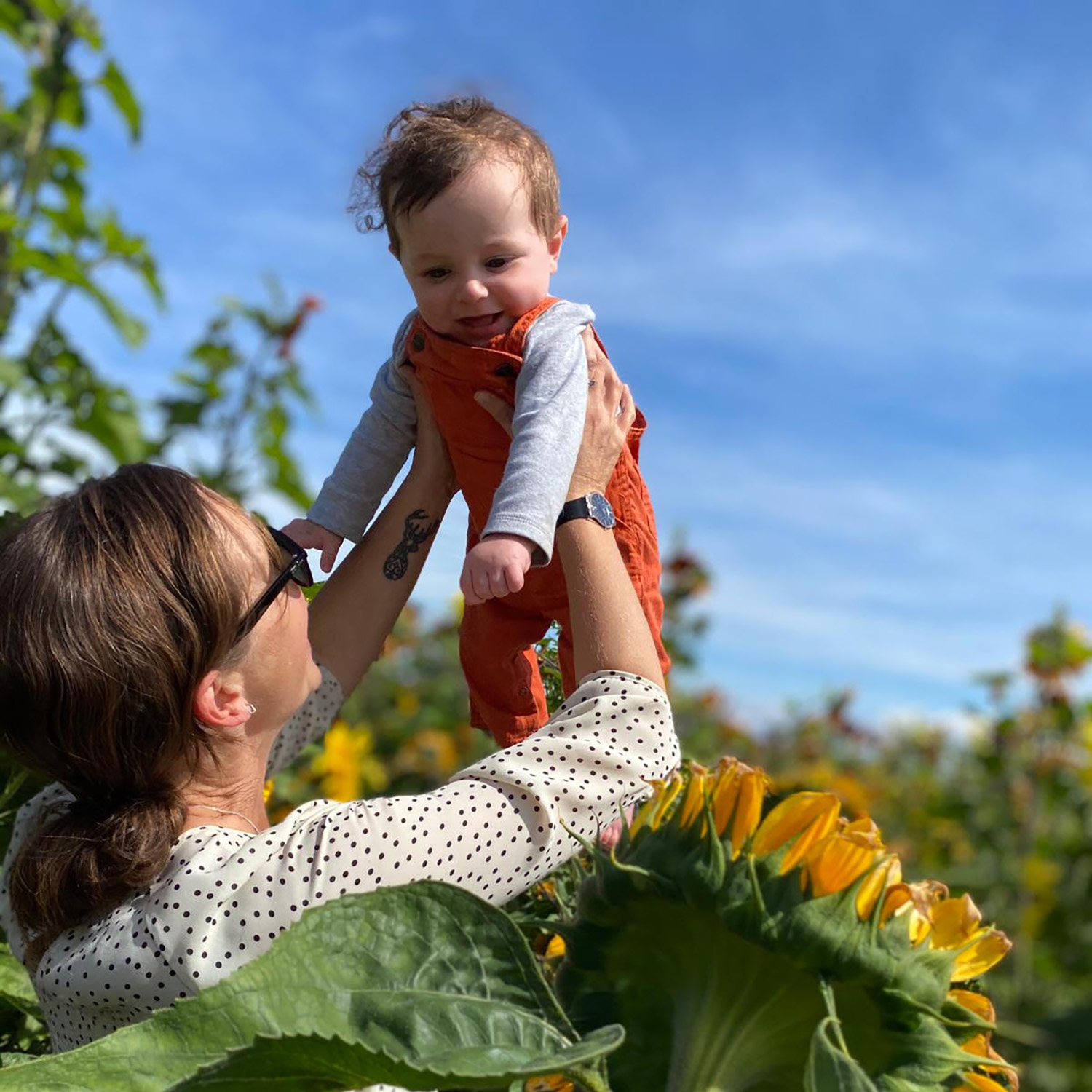 a mom holds her baby up to the sky in a patch of sunflowers