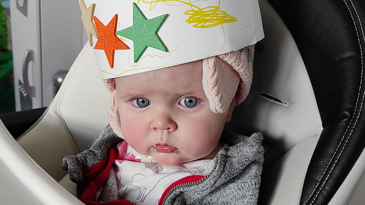 a baby in their high chair wearing a paper crown with stars on it