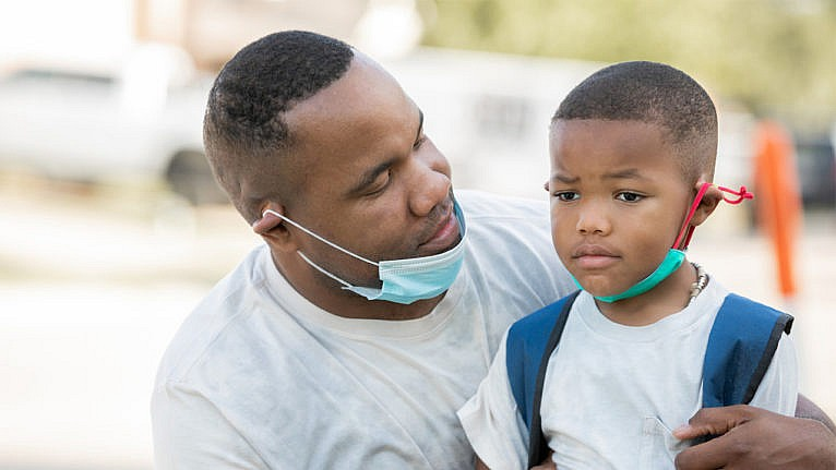 A nervous looking boy with his mask under his chin wearing a backpack is consoled by his dad