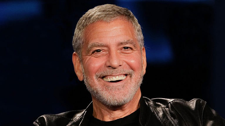 George Clooney smiling at the camera in a leather jacket