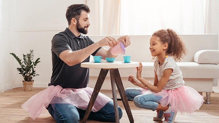 a man in a tutu having a tea party with his daughter who is also in a tutu