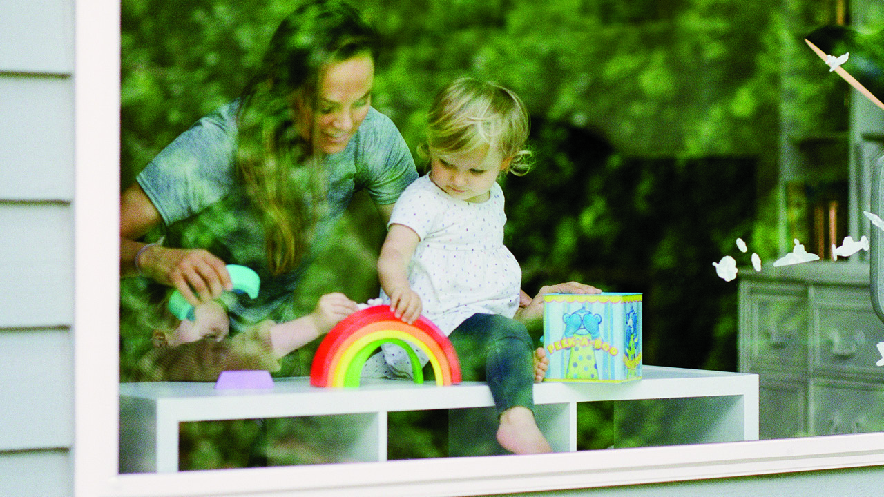 a mom and her child behind their front window playing with a rainbow