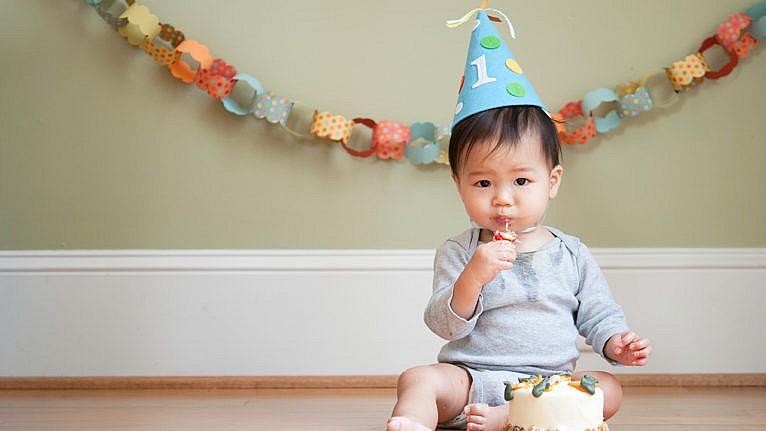 a baby sitting on the floor with a little carrot cake wearing a birthday hat with a 1 on it with paper chain hung on the wall behind him for a story on pandemic babies