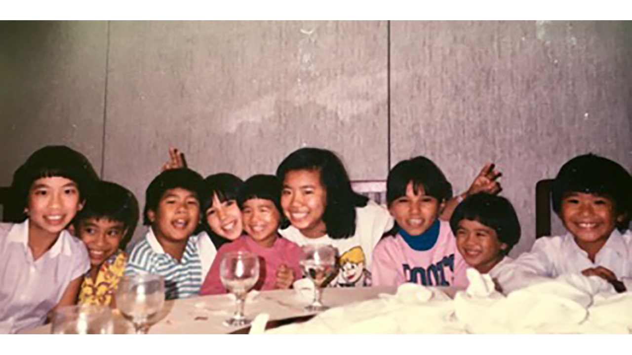 nine cousins pose together at a dinner table in an older photo from the 70s or 80s