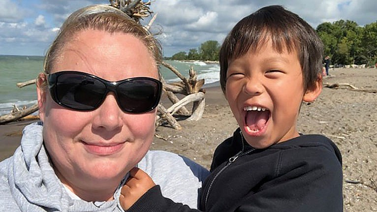 A mom and her school-aged son on the beach