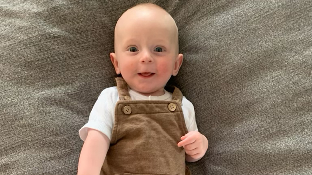 A beaming baby in brown overalls lying on their back