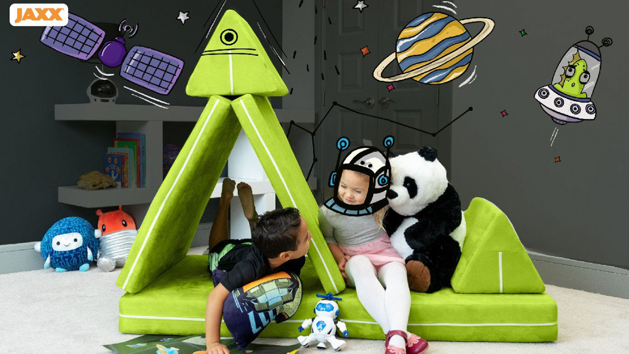 Photo of two kids playing on a modular play couch set up like a space ship