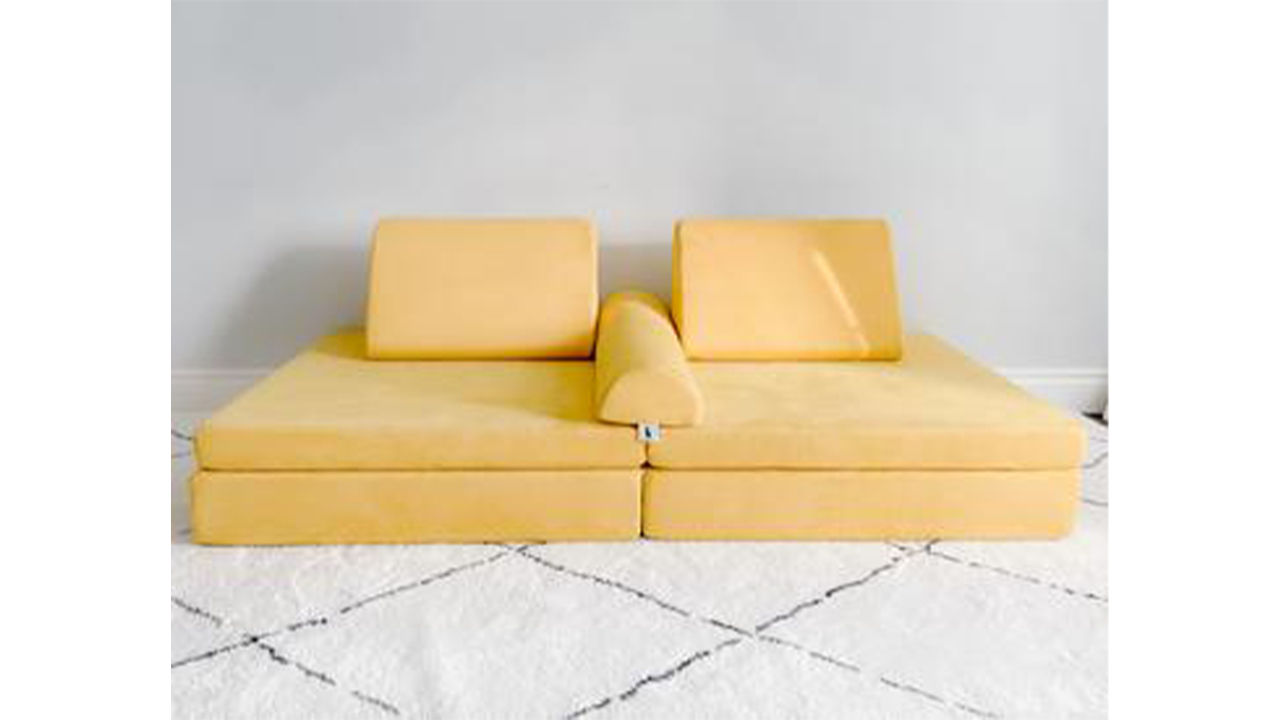 Photo of a yellow play couch on a rug
