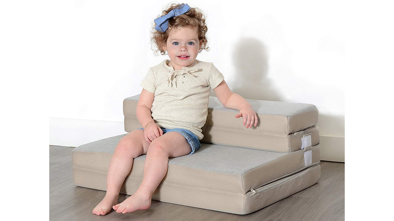Photo of a toddler sitting on a foldable cushion couch