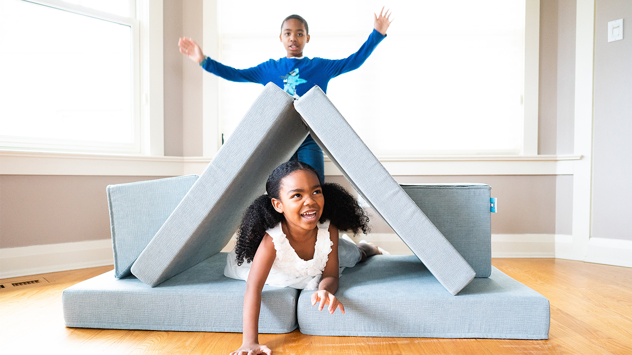 Photo of two kids crawling through a tunnel made by two cushions from aplay couch