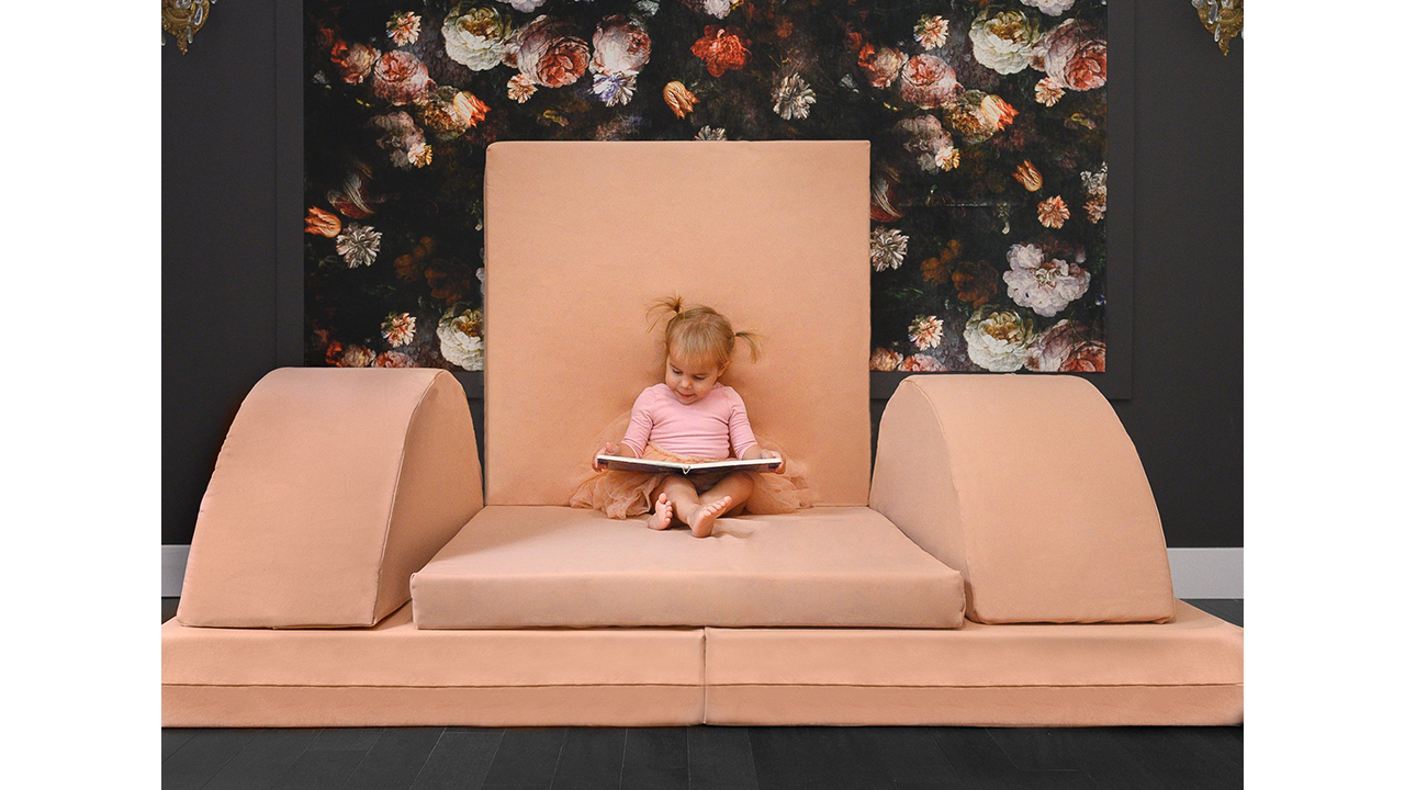 Photo of a young kid reading a book on a play couch arranged to look like a throne