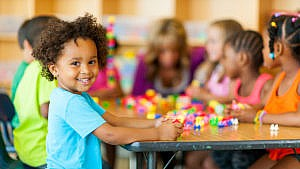 a little boy smiles at the camera from his table full of kids at daycare