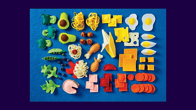 An assortment of felt foods including broccoli, avocado, pasta, eggs, cheese, meat, carrots, blueberries, peas and chicken drumsticks