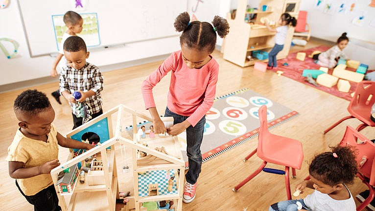 Children play at tables and with a doll house in a brightly coloured daycare for a story on the national childcare plan