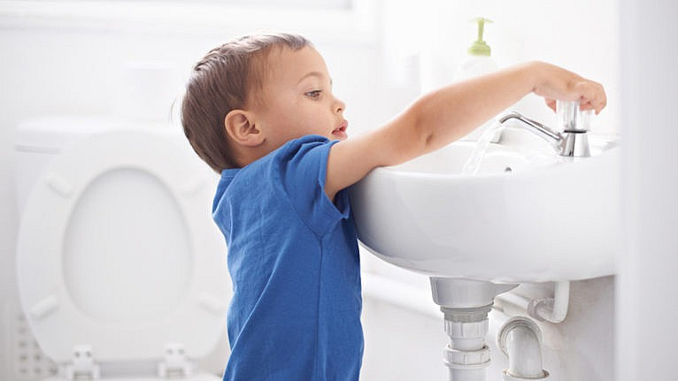 A little boy washing his hands after going to the bathroom for a story on bathroom independence