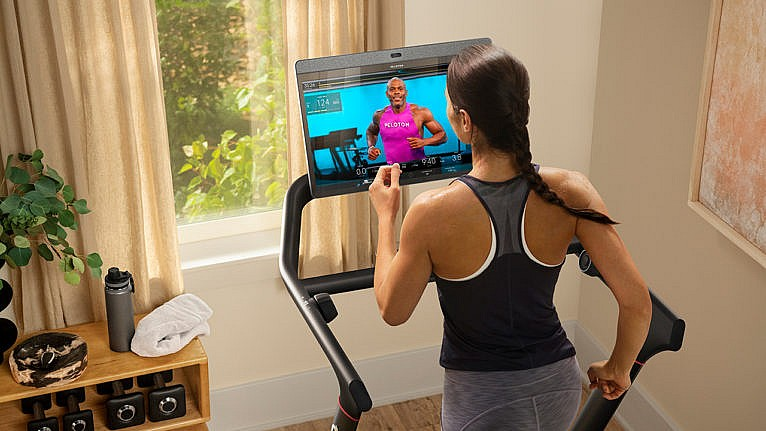 A woman runs on the peloton tread with an instructor on the screen in front of her