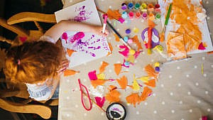 Overhead photo of a kid doing a messy painting craft