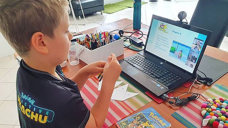 photo of a kid in front of a laptop participating in a Pokémon themed lesson through the Outschool platform