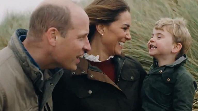 Still from a video posted for Will and KAte's anniversary showing the couple laughing with their youngest kid while sitting by the shore