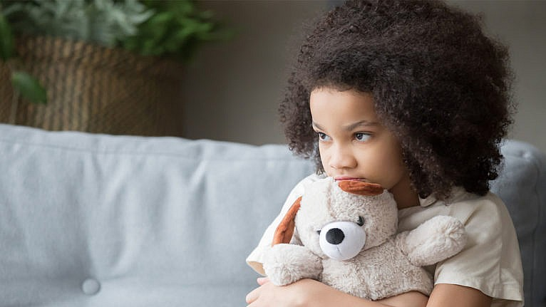 a little girl hugs her stuffie while looking sadly out the window for a story on covid's effects on kids