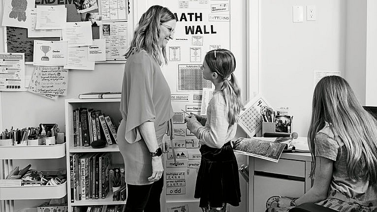 Photo of a mom and her two kids in front of a math wall