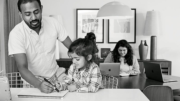 Photo of a dad helping his kid with schoolwork while mom works on her laptop in the background