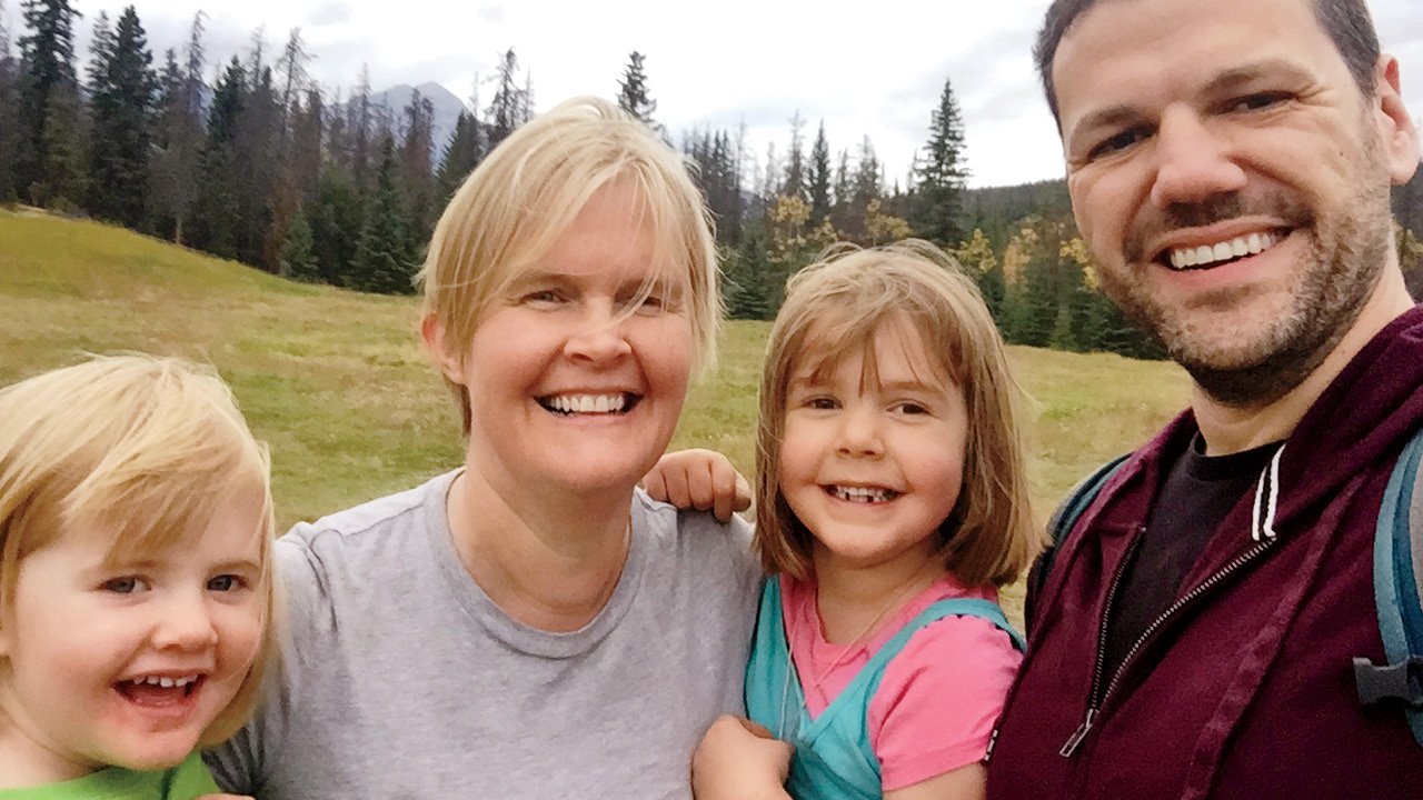 A selfie of a family in front of some scenic trees and mountains