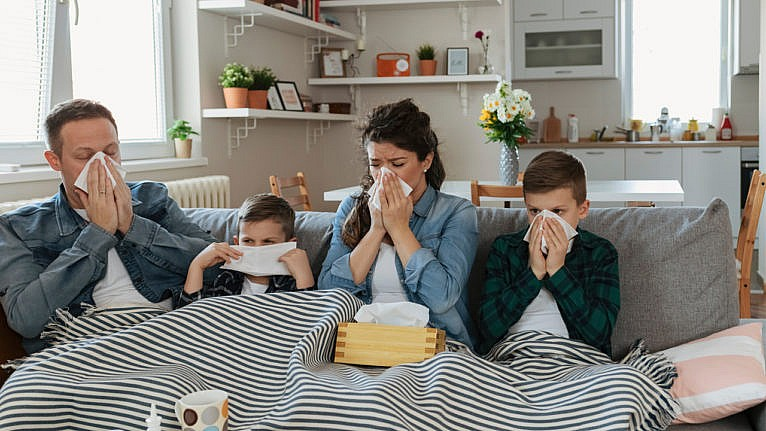 a young family who are all sick sit on the couch blowing their noses