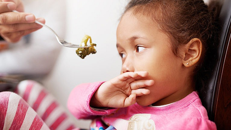 Photo of a kid covering their mouth with their hand while an adult holds a piece of broccoli in front of them with a fork