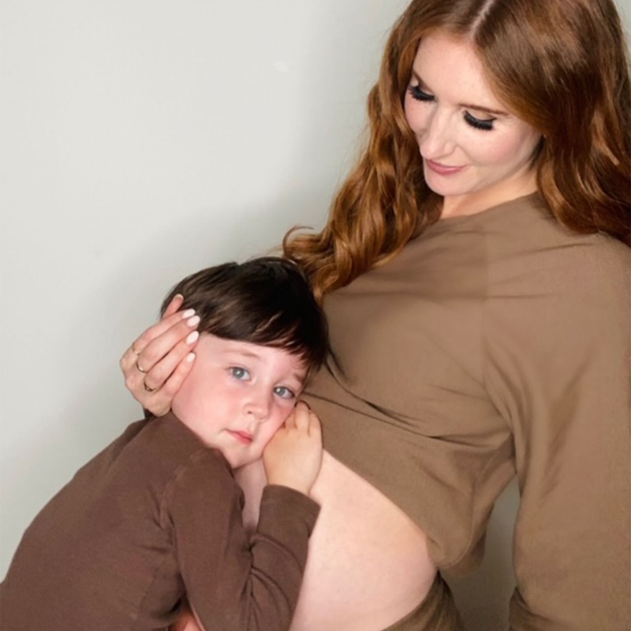 Photo of Jessi Cruickshank hugging one of her kids while they hug her pregnant belly