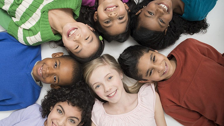 A diverse group of elementary age students are lying in a circle together and are smiling while looking up at the camera.