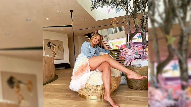 Image of Chrissy sitting in her home next to a tree