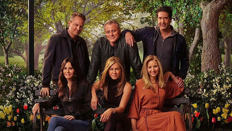 The cast of Friends - Matt LeBlanc, David Schwimmer, Matthew Perry, Jennifer Aniston, Courteney Cox and Lisa Kudrow - post on and around a bench in a promo photo for Friends: The Reunion