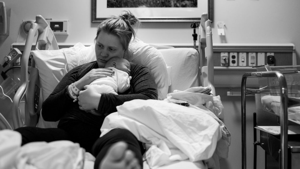 black and white image of mom holding her new baby in a hospital bed