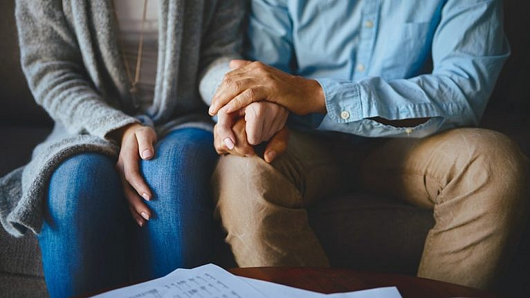 sitting couple holds hands in front of a table of papers