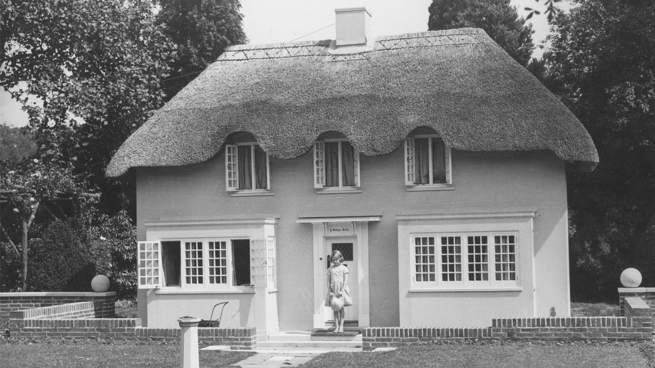 Princess Elizabeth posting in front of her life-size playhouse in 1933