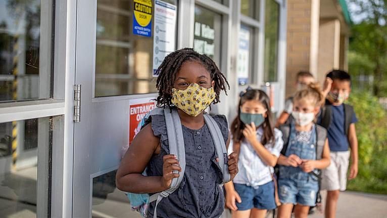 Photo of kids lined up at school while wearing face masks