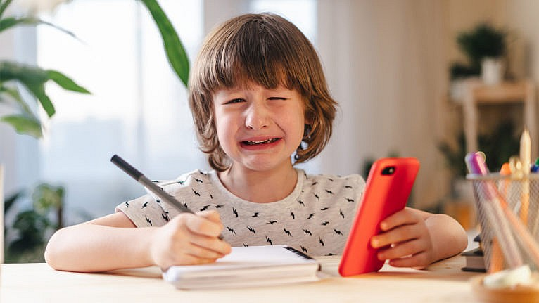 young boy crying while doing remote learning