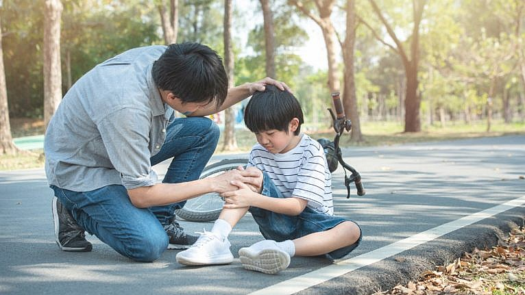 A father consoles his child who has sustained an injury after falling off his bike.