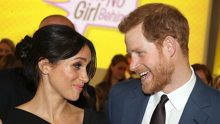 prince harry and meghan markle look playfully at each other