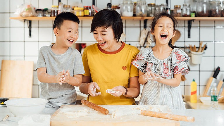 A parent and two kids laughing while making food.