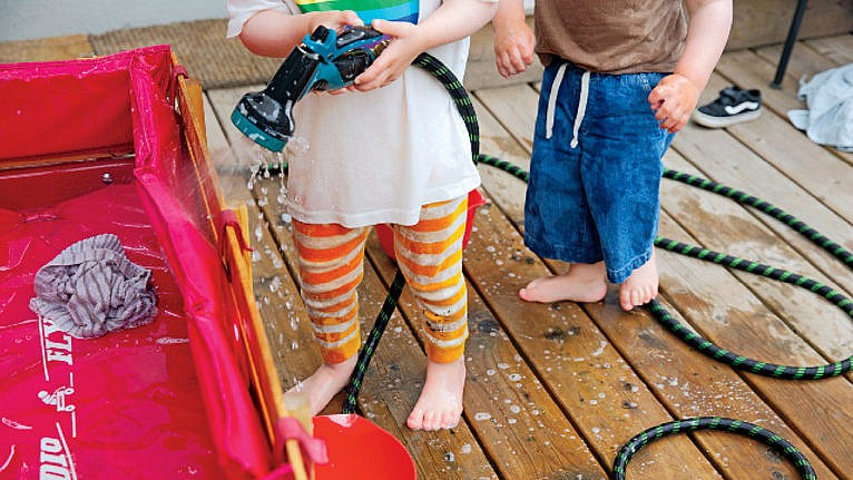 photo of two young kids on a deck playing water and a hose