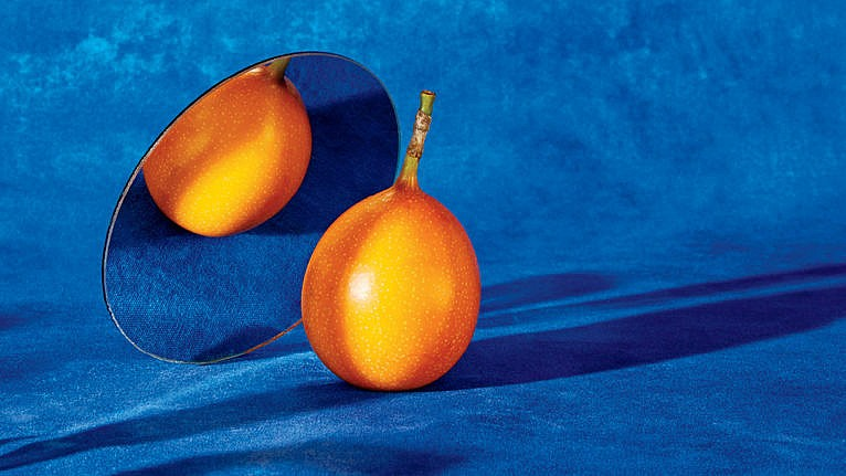 a photo of an orange in front of a mirror with a blue backdrop