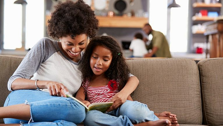 a black mom and daughter sit on the couch reading