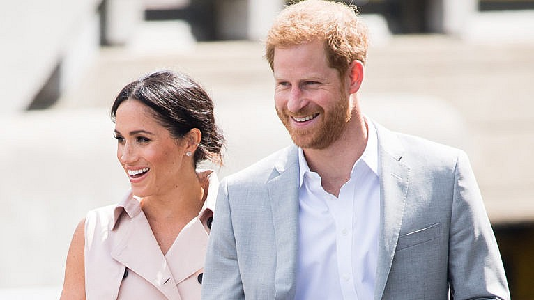 Prince Harry and Meghan smile while walking in London