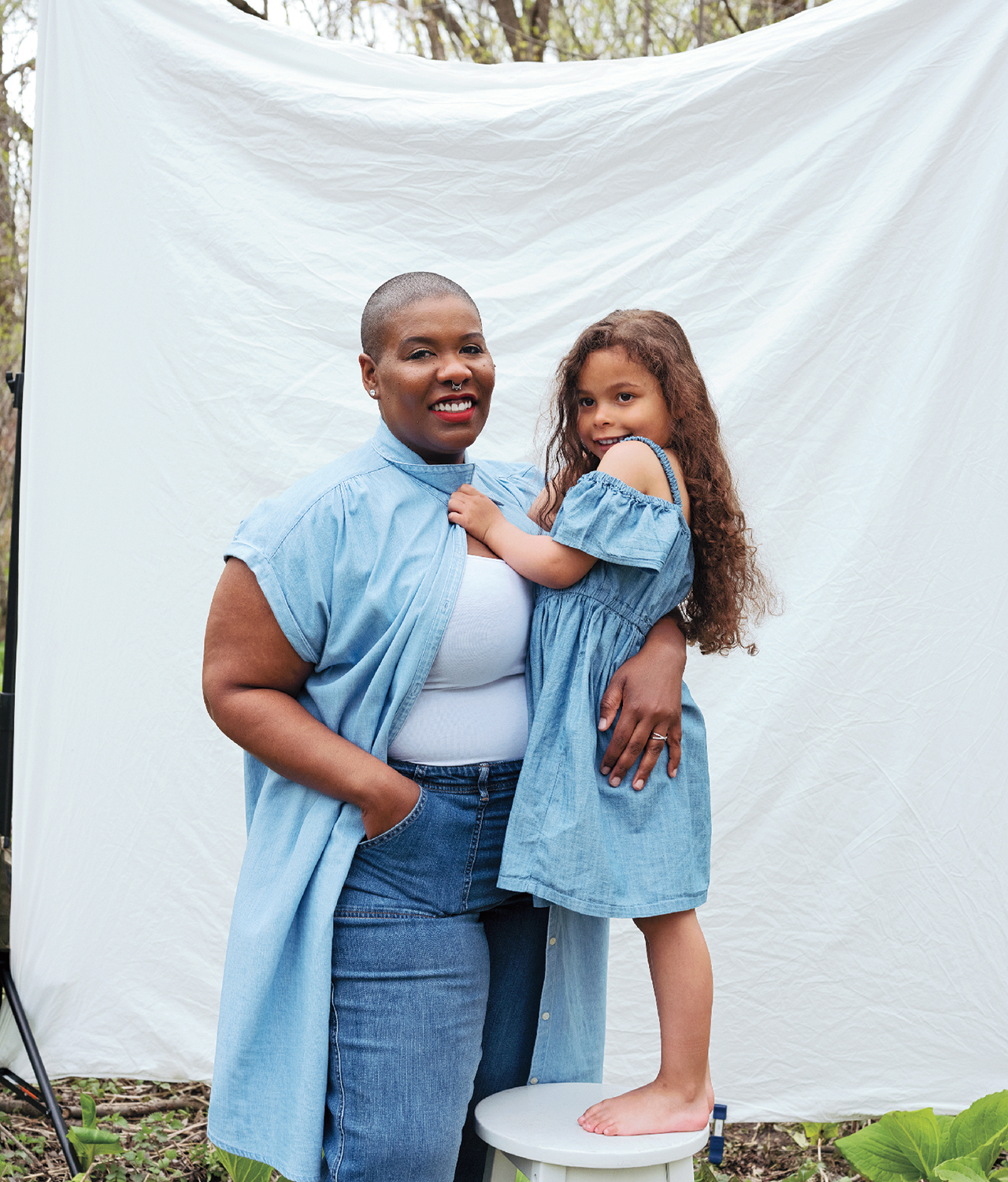 a mother and her preschool-aged daughter, who is standing on a stool, pose for the camera in an embrace